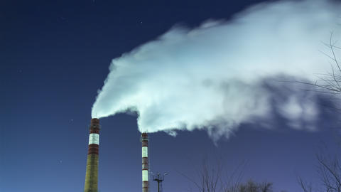 Smoking Chimneys Against the Night Sky and Stars Air Pollution and the Environment Live Action
