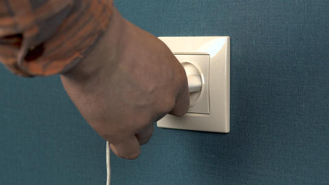 A Man Pulls Out a Phone Charger From a Wall Outlet Rosette in the Wall with Dark Blue Wallpaper 2 Live Action