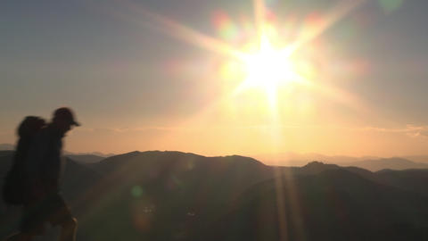 Silhouetted man walks past sun flare over mountain layers Live Action