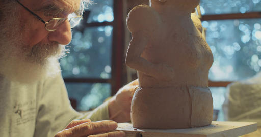 Old artist working in his studio modeling clay sculptures Footage
