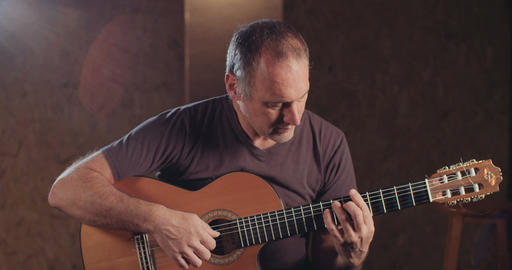 Musician playing an acoustic guitar in a recording studio Footage