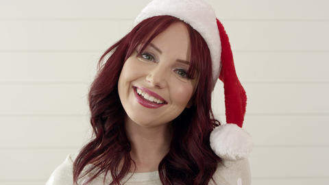 Up close of attractive red headed woman wearing christmas stocking hat Live Action