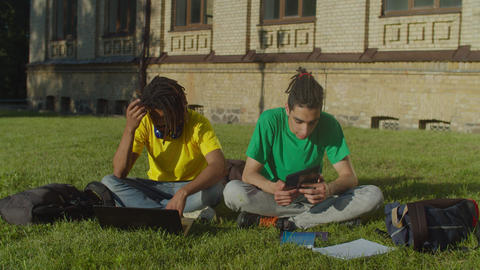 Multiethnic male students learning with gadgets Live Action