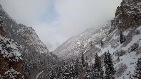 Aerial view flying backwards in snowy canyon Live Action