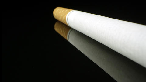 Up close view of single cigarette on black reflective surface Live Action