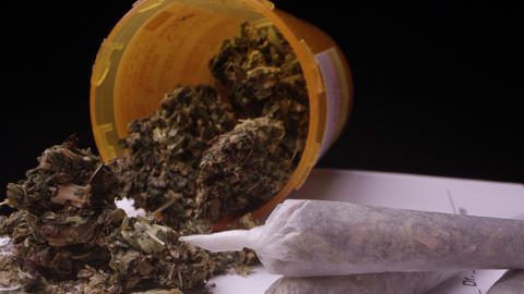 Zooming in looking at medical marijuana in bottle and joints Live Action