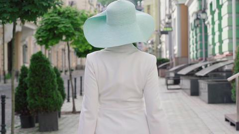 Camera follows confident fashionable lady walking on sunny urban street, turning Live Action