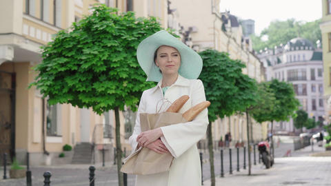 Stylish lady in elegant hat standing on city street with baguettes. French Live Action