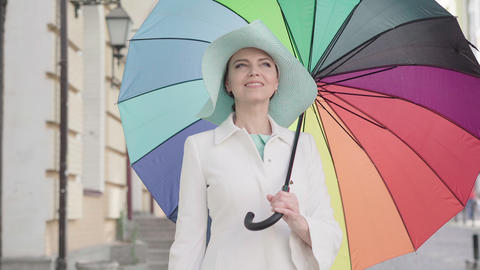 Camera approaches to elegant adult Caucasian woman standing outdoors with Live Action