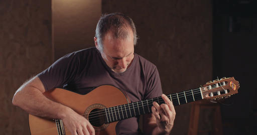 Musician playing an acoustic guitar in a recording studio GIF