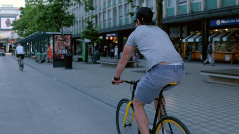 Young hipster riding his fixed gear bike on the city streets and doing a wheelie Footage