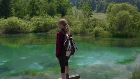 Tracking shot - Female standing at Zelenci Springs looking at the natural beauty Footage