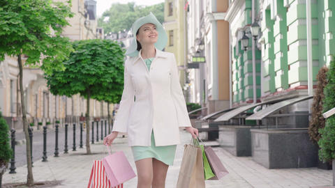 Portrait of beautiful mid-adult Caucasian woman in elegant hat and coat walking Live Action