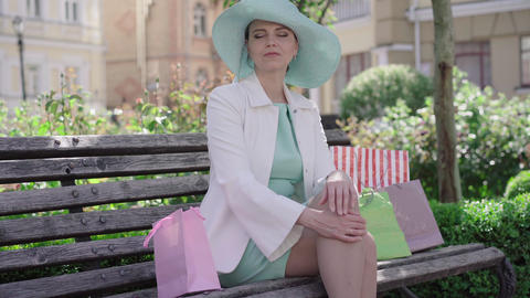 Elegant tired woman taking off turquoise hat and waving. Portrait of Caucasian Live Action