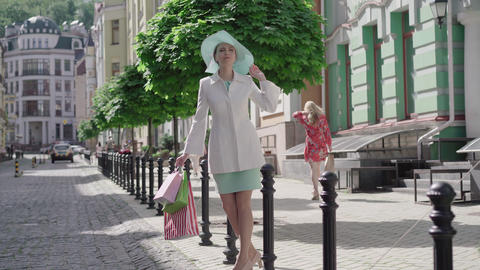 Wide shot portrait of elegant woman crossing the street. Beautiful mid-adult Live Action
