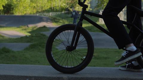 person in gumshoes rides bike past spirea bush in garden Live Action