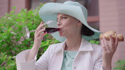 Portrait of attractive woman drinking red wine and smelling tasty croissant Live Action