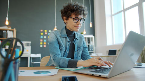 Serious woman using laptop in creative office working at desk alone typing Live Action