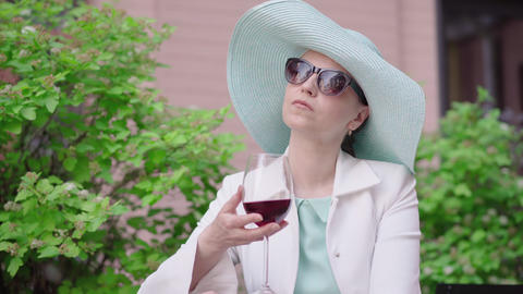 Confident woman in stylish hat and sunglasses drinking red wine outdoors Live Action