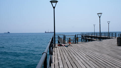 Shot of the pier and open sea on a clear day. Blue sky, pier, ships in the distance and boundless Live Action