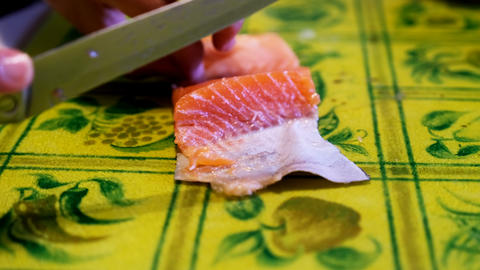 Woman cuts fish fillet, cook prepares fish for cooking, fish dishes, healthy and diet food Live Action