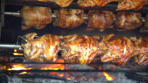 Grilled Rotisserie Chicken - Roasted chickens on spit grilled over wood fire on Live Action