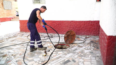July 13, 2020. Granada. Spain: Worker cleans the drains hatch and removes dirt Live Action