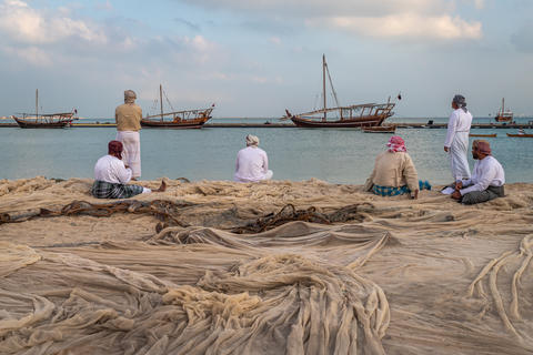 Traditional Arabic fishermen sitting and standing on Katara beach Doha, Qatar フォト