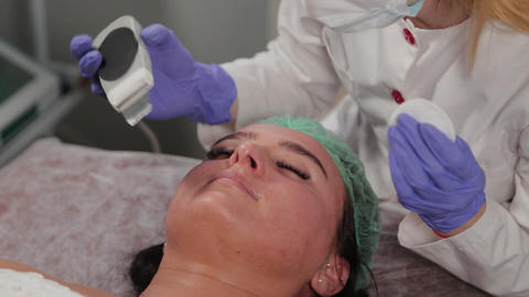 Professional cosmetologist woman doing ultrasonic face cleaning to patient Live Action