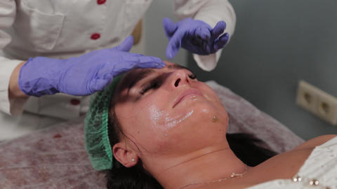Professional beautician washes a woman and massages her face Live Action