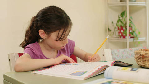 Young girl having difficulties preparing homework Footage