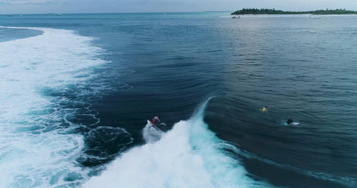 Tracking shot over surfers catching waves or surf on surfing at wild tropical Live Action