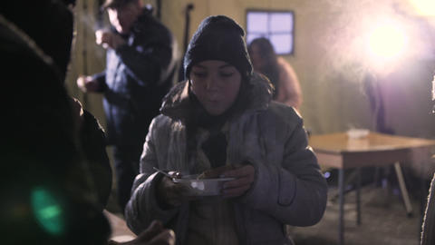 woman in jacket and hat eats food on street in cold winter Live Action