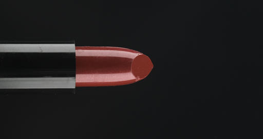 Closeup of rotates lipstick. Twist and put forward red lipstick on black Live Action
