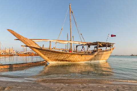 Traditional wooden boat (dhow) in Arabic gulf with Qatari flag フォト