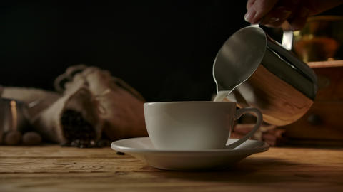 Pouring frothed milk into coffee cup. Latte art from metal modern pitcher Live Action