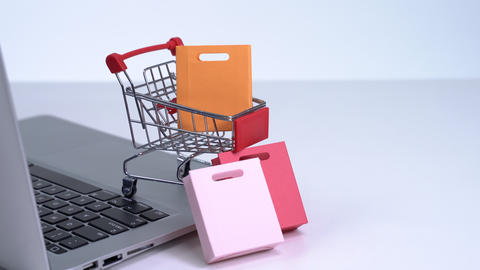Online shopping. Mini shop cart trolley with colorful paper bags and laptop computer on white table Live Action