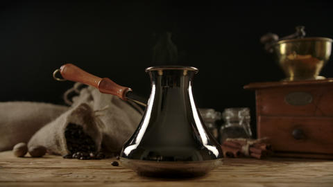 Traditional coffee cezve with wooden handle on wooden desk. Dolly shot Live Action