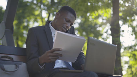 Portrait of dissatisfied African American businessman sitting in sunny park with Live Action