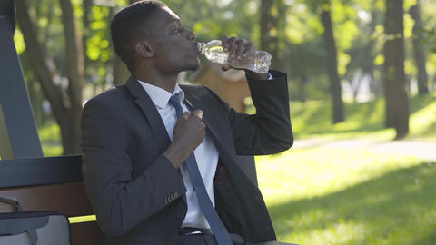 Camera approaches to happy African American man drinking fresh cold water Live Action