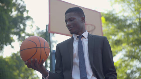 Portrait of elegant African American businessman posing with ball on basketball Live Action