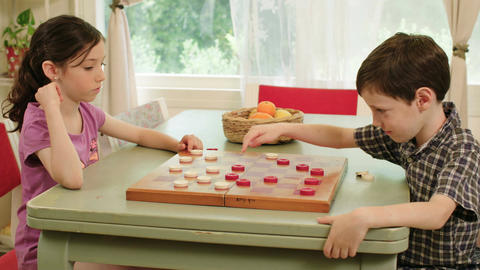Two kids playing checkers at home Footage