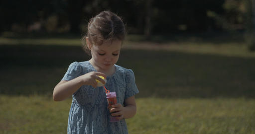 Little girl wearing a blue dress blowing soap bubbles outside Footage