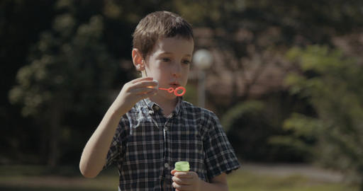 young boy blowing soap bubbles Footage