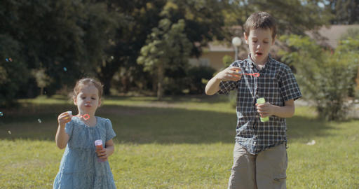 young boy and little girl blowing soap bubbles outside Footage