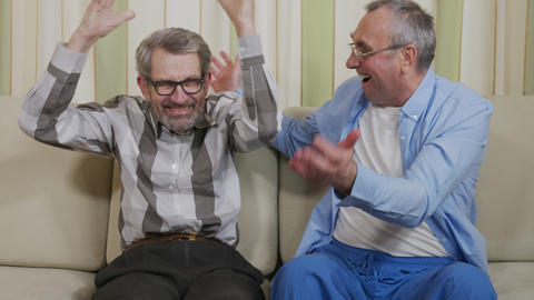 Cute Attractive elderlyMale Gay Couple Sit Together on a Sofa at Home Live Action