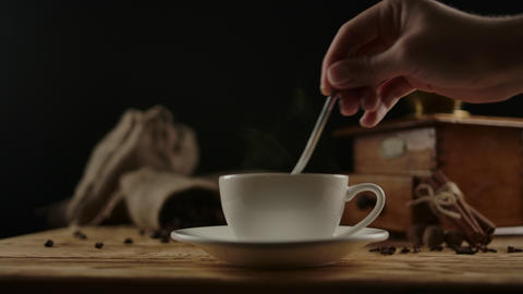 Elegant female hand neatly stirring hot drink in stylish coffee or tea cup Live Action