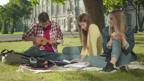Positive Caucasian man playing ukulele for beautiful girls on sunny green meadow Live Action