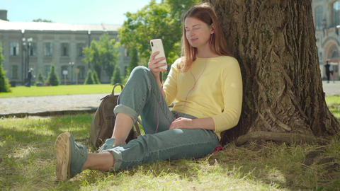 Cheerful redhead girl using video chat outdoors on sunny summer day. Portrait of Live Action