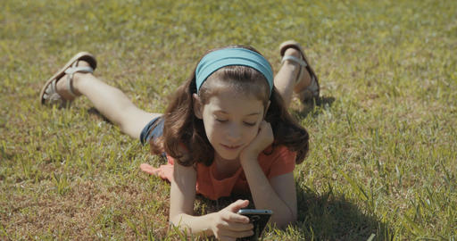young girl laying on the grass outside, playing with a mobile phone Footage